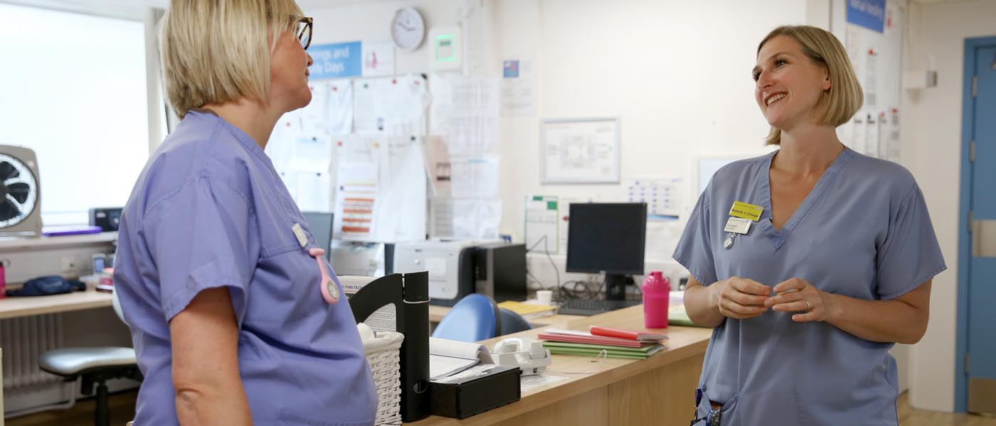 Picture of two maternity nurse standing in a room talking to each other