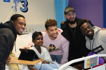 Picture of a four males tanding around a hospital bed in which there is a child