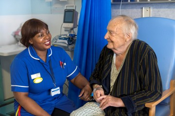 Picture of nurse talking to a patient who are both sitting down in a hospital environment