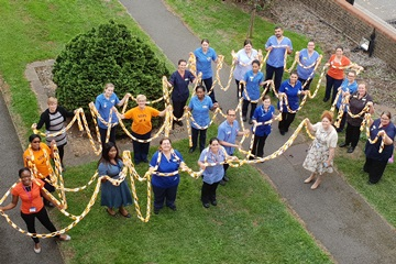 Picture of staff standing on grass holding a large paper chain