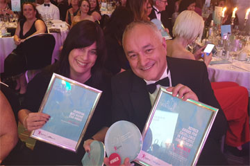 Picture of Paul da Gama and Tania Marcus at an awards ceremony holding the awards they won